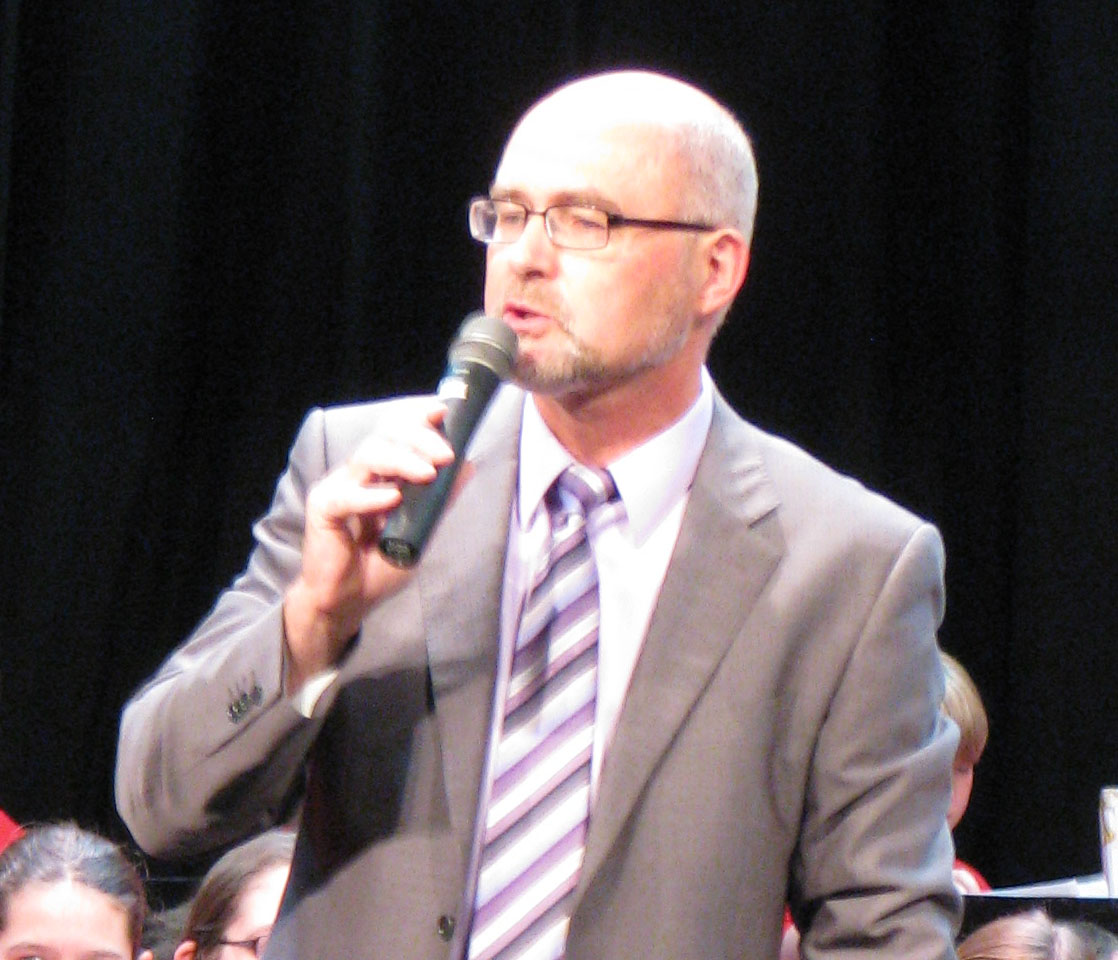 Photo of Bill Simon speaking at a concert